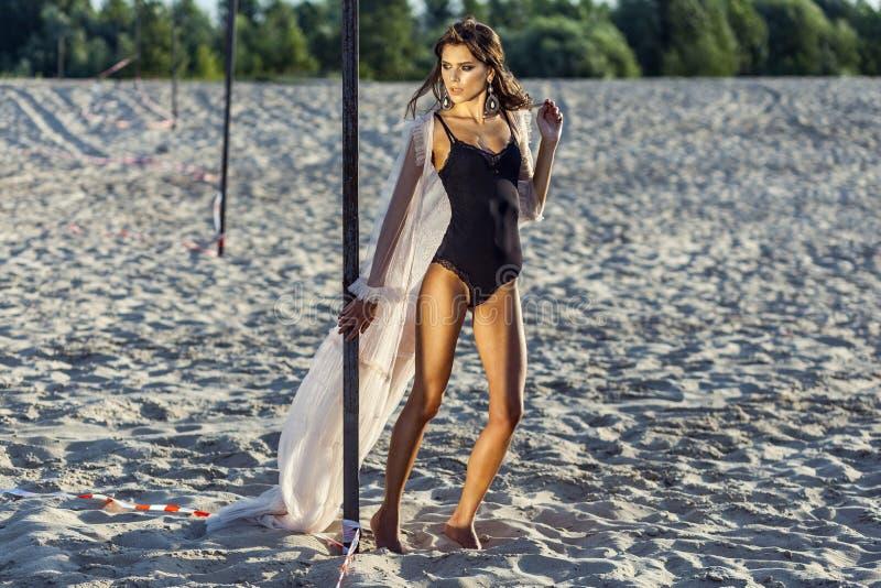 De aantrekkelijke donkerbruine vrouw in zwart lichaam en het doorzichtige strand behandelen omhoog het stellen op zandig strand b royalty-vrije stock afbeelding