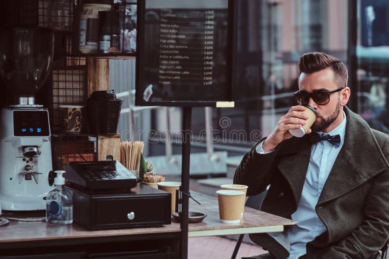 De aantrekkelijke elegante mens in zonnebril drinkt zijn koffie terwijl het zitten buiten bij coffeeshop stock afbeelding