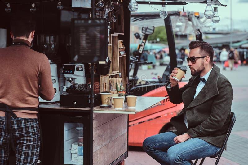 De aantrekkelijke elegante mens in zonnebril drinkt zijn koffie terwijl het zitten buiten bij coffeeshop stock foto's