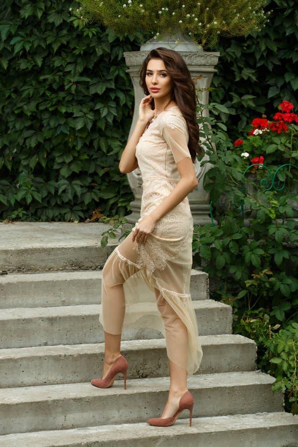 De aantrekkelijke en elegante rijke jonge dame in kleding stelt op treden van mooi landgoed in park stock foto's