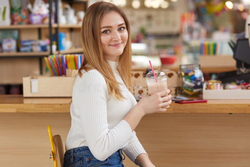 De aantrekkelijke Europese vrouw houdt milkshake, geniet van vrije tijd, gekleed in witte verbindingsdraad en jeans, tevreden met stock fotografie