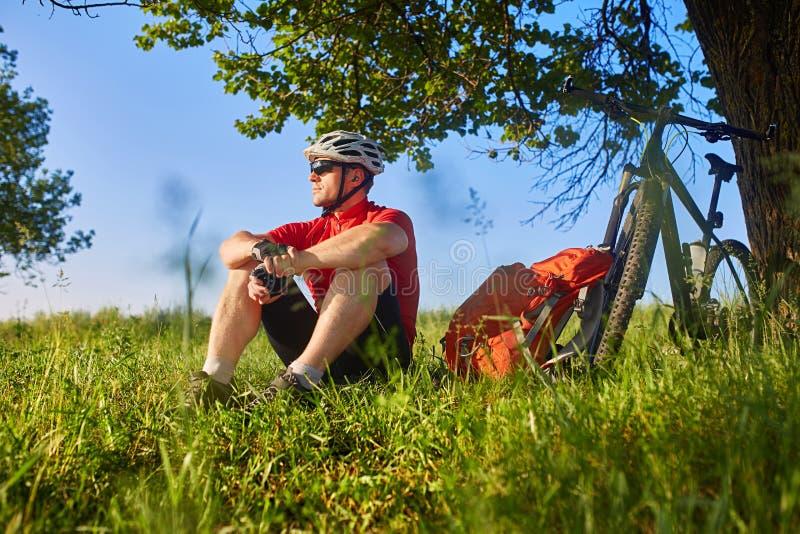 De aantrekkelijke fietserzitting op het gras dichtbij de fiets en nadert de boom royalty-vrije stock fotografie