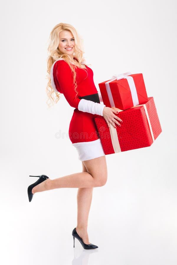De aantrekkelijke gelukkige vrouw in rode het kostuumholding van de Kerstman presen royalty-vrije stock foto's