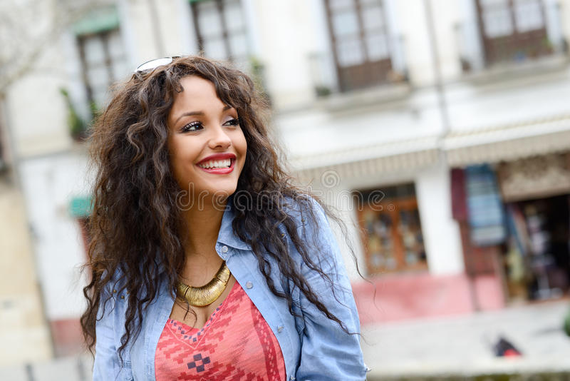 De aantrekkelijke gemengde vrouw in het stedelijke toevallig dragen als achtergrond kleedt zich royalty-vrije stock afbeeldingen