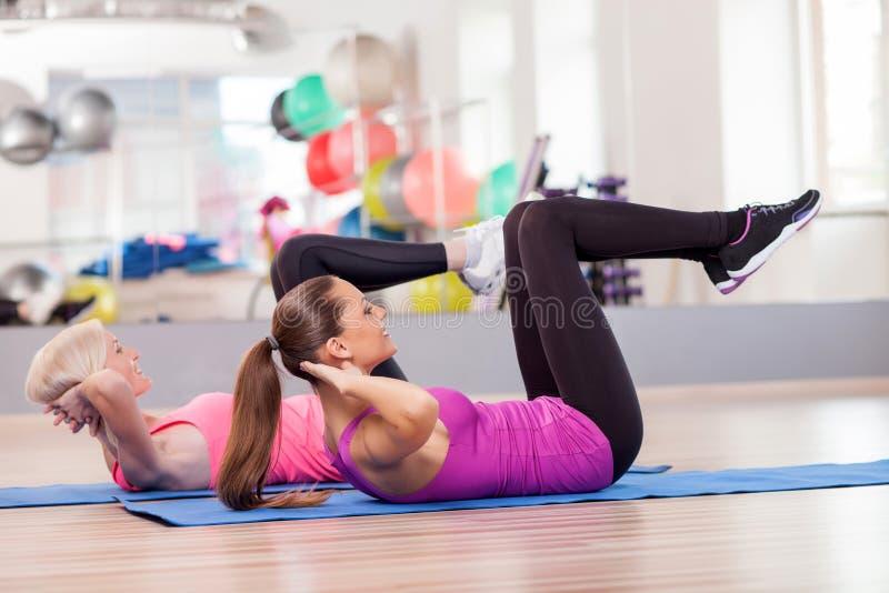 De aantrekkelijke geschikte dames oefenen in gymnastiek uit stock fotografie