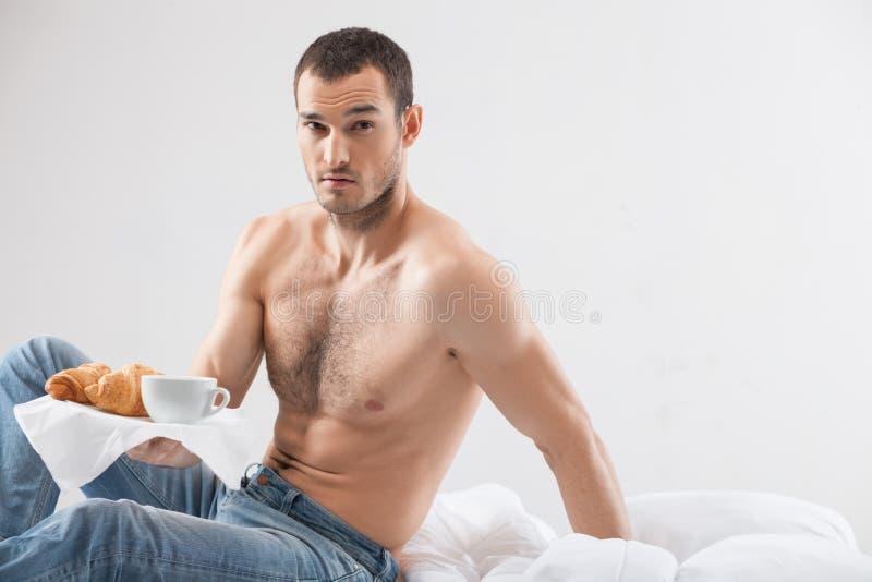 De aantrekkelijke geschikte kerel dient voedsel in slaapkamer stock foto