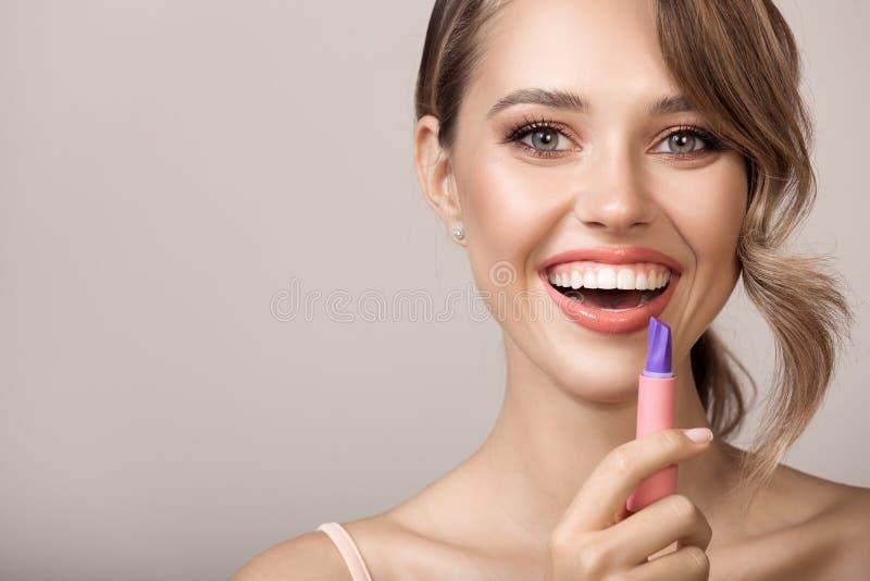 De aantrekkelijke het glimlachen lippenstift van de vrouwenholding ter beschikking stock fotografie