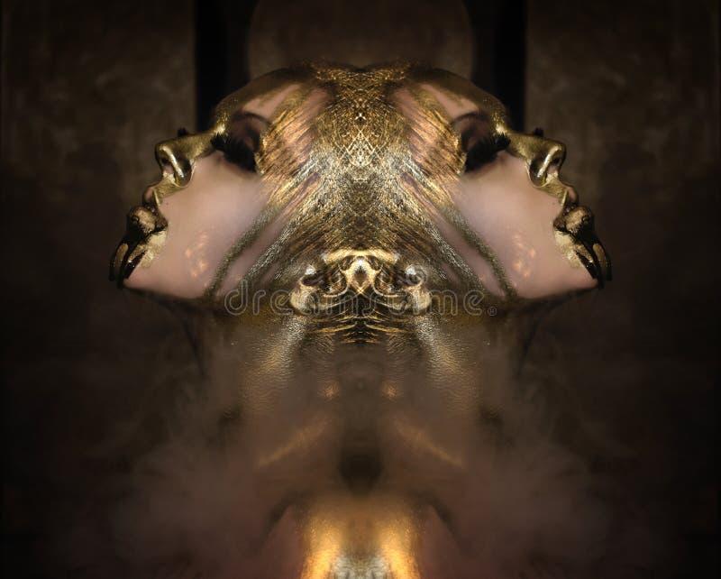 De aantrekkelijke hete vrouw met mooi vloeibaar goud op haar gezicht en lichaam stelt donkere achtergrond in rook, gesloten ogen royalty-vrije stock foto