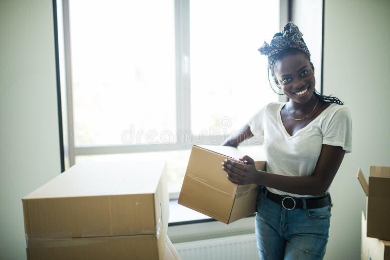 De aantrekkelijke jonge Afrikaanse vrouw beweegt zich, bekijkt elkaar en glimlacht terwijl status onder kartondozen verhuizing royalty-vrije stock fotografie