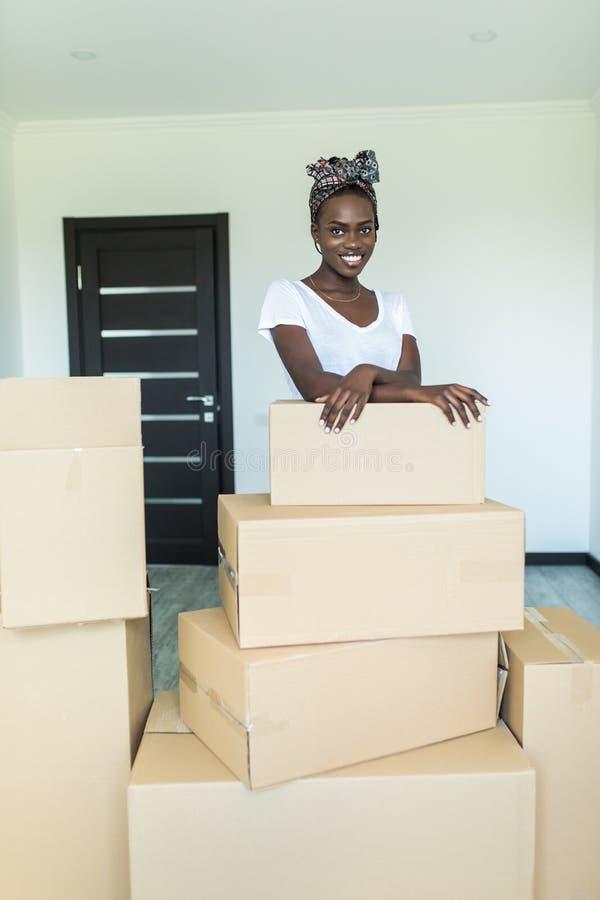 De aantrekkelijke jonge Afrikaanse vrouw beweegt zich, bevindt zich onder kartondozen, bekijkt camera en glimlacht royalty-vrije stock afbeelding