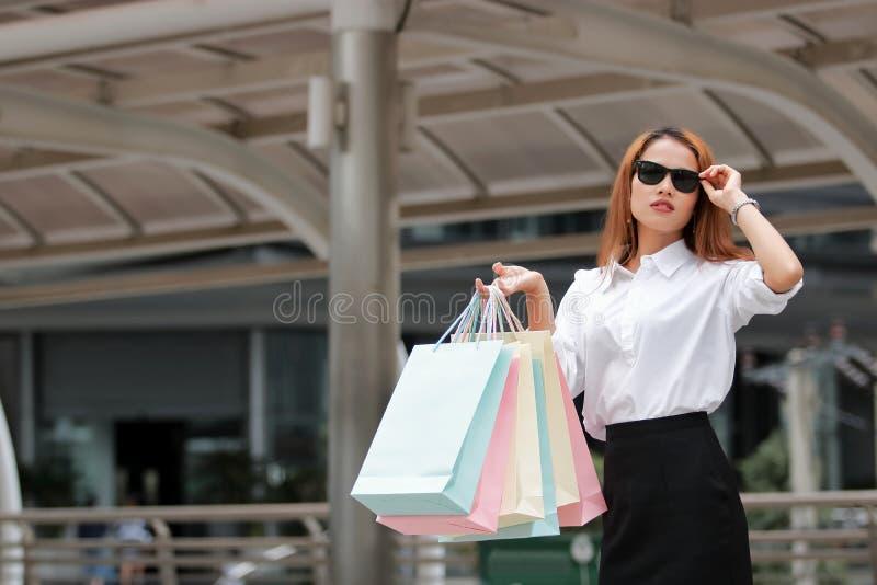 De aantrekkelijke jonge Aziatische vrouw in vrijetijdskleding die het kleurrijke winkelen dragen doet in openlucht in zakken royalty-vrije stock foto