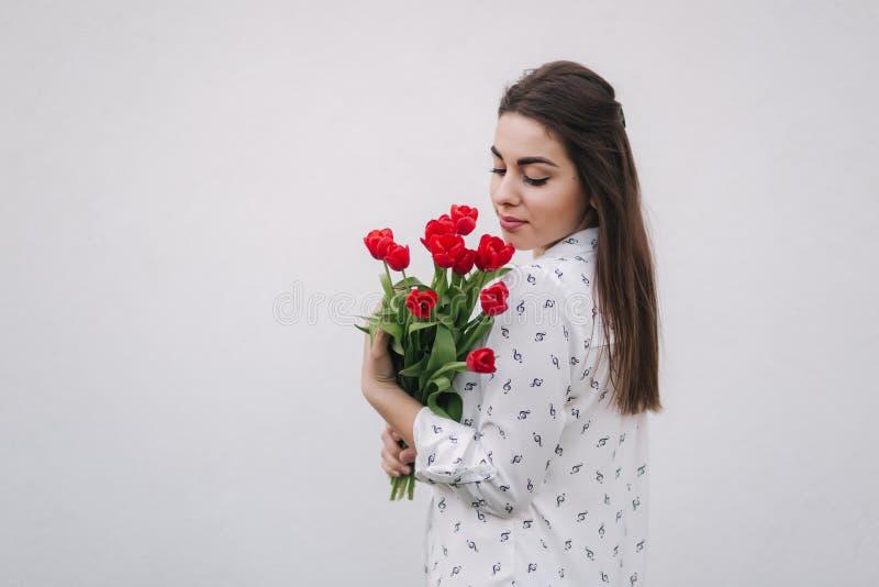 De aantrekkelijke jonge dame in wit overhemd houdt een boeket van rode bloemen Witte achtergrond stock foto
