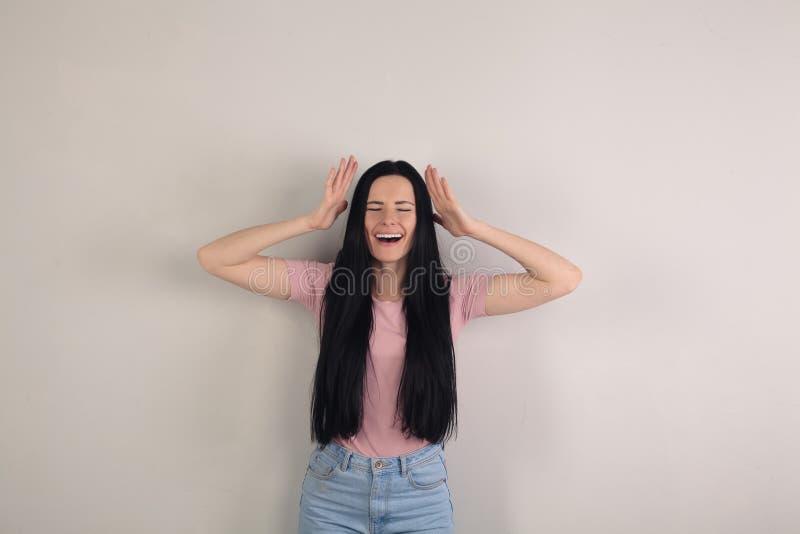 De aantrekkelijke jonge donkerbruine vrouw met lang haar bevindt zich door de grijze achtergrond die haar handen omhoog houden do royalty-vrije stock fotografie