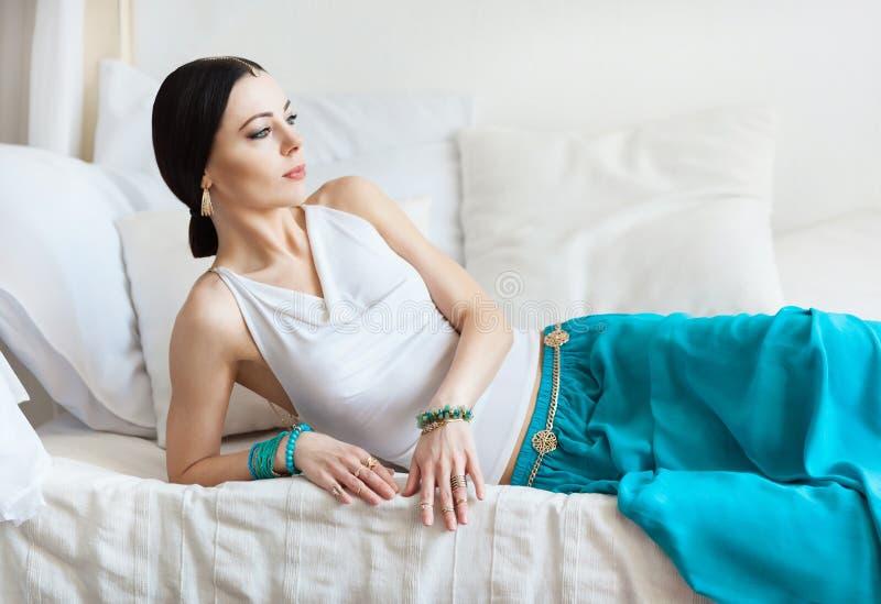 De aantrekkelijke jonge gelooide vrouw in oosterse juwelen ligt op een wit bed royalty-vrije stock foto's