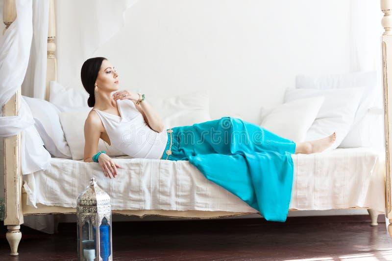 De aantrekkelijke jonge gelooide vrouw in oosterse juwelen ligt op een wit bed royalty-vrije stock fotografie