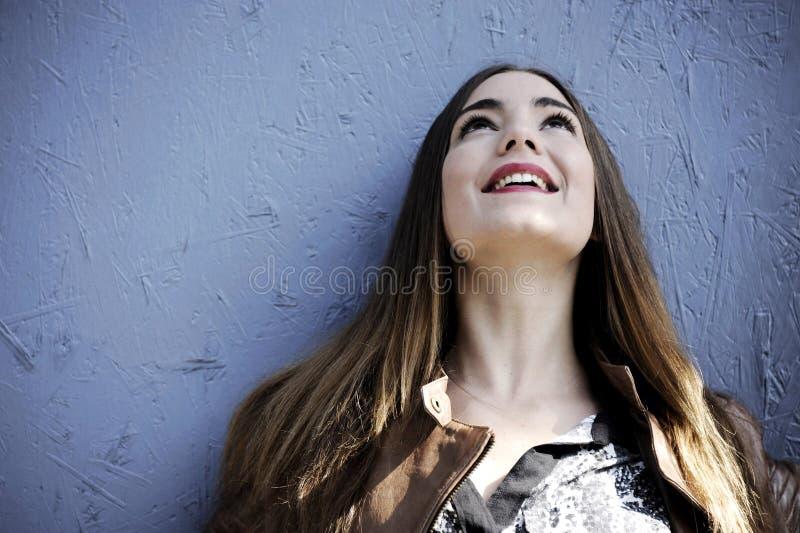 De aantrekkelijke jonge hipstervrouw bevindt zich tegen een blauwe houten muurachtergrond met emoties op haar gezicht royalty-vrije stock fotografie