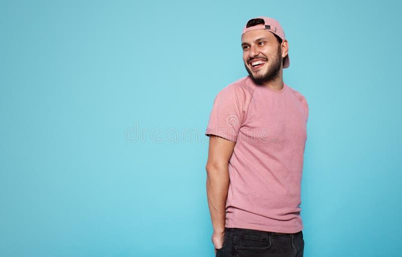 De aantrekkelijke jonge jongensglimlachen gelukkig, heeft uitdrukking opgewekt, dragend roze t-shirt en honkbal GLB, dat over bla stock foto