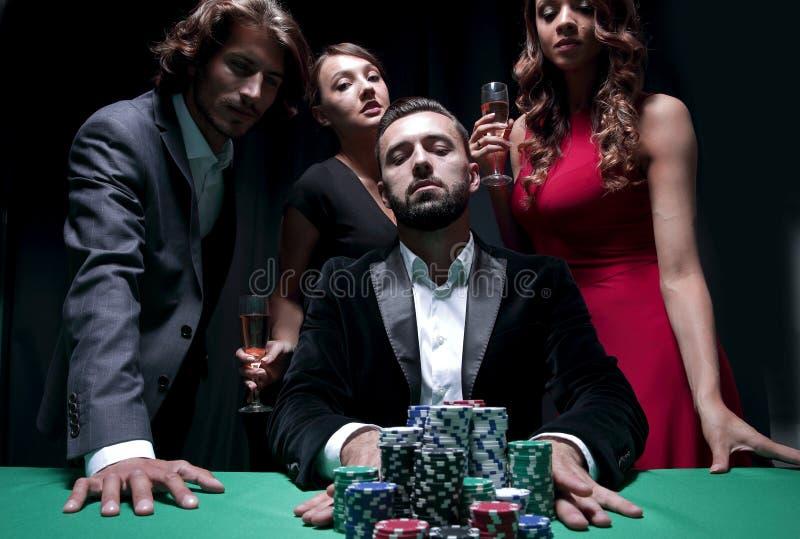 De aantrekkelijke jonge Kaukasische mens maakt weddenschap in het casino stock afbeeldingen