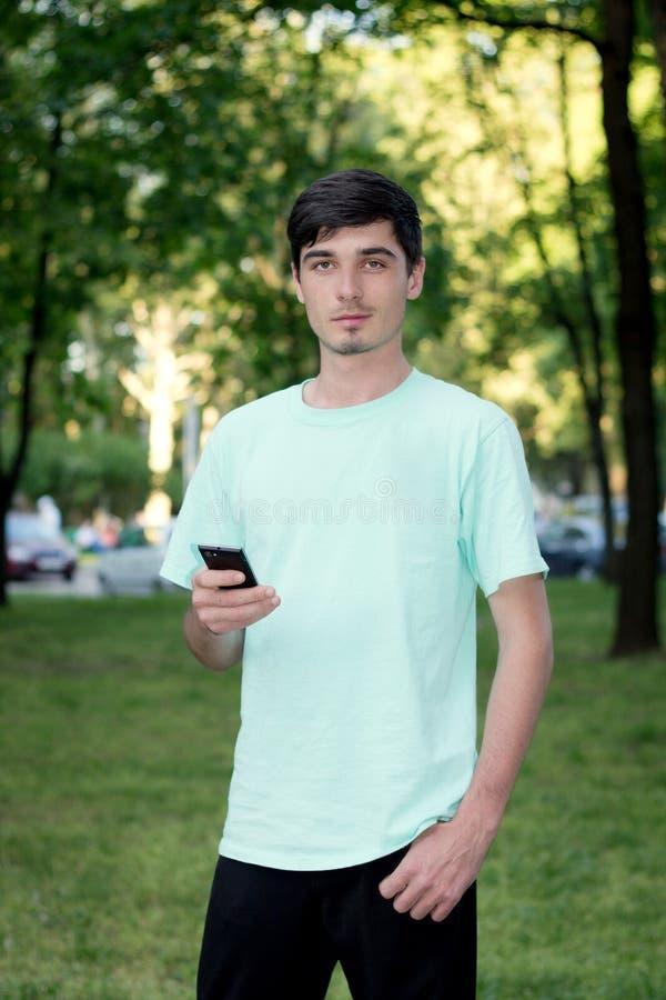 De aantrekkelijke jonge kerel roept in openlucht telefonisch royalty-vrije stock foto