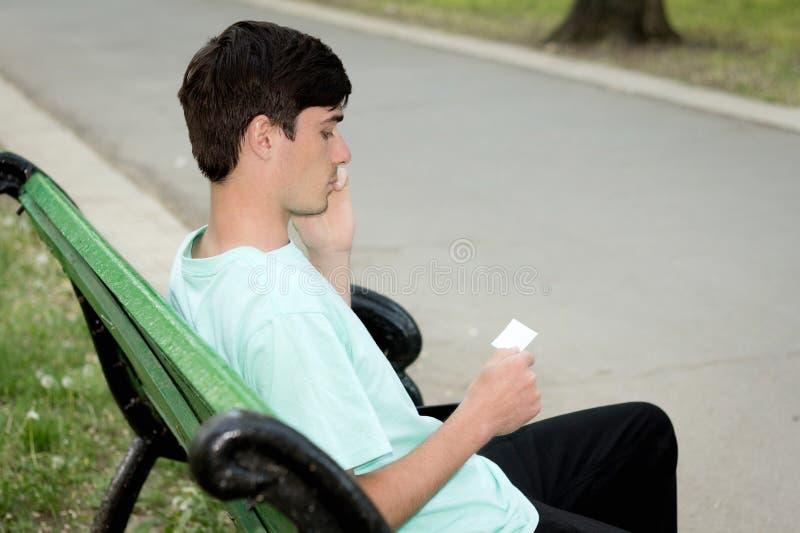 De aantrekkelijke jonge kerel roept in openlucht telefonisch stock foto's