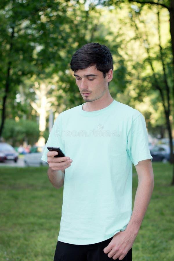De aantrekkelijke jonge kerel roept in openlucht telefonisch royalty-vrije stock foto's