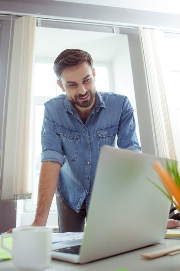 De aantrekkelijke jonge kerel werkt aan computer royalty-vrije stock fotografie