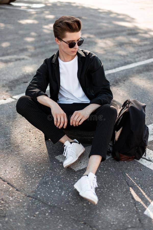 De aantrekkelijke jonge mens in een elegant overhemd in modieuze zonnebril in broek met een rugzak in in tennisschoenen zit op he stock afbeelding
