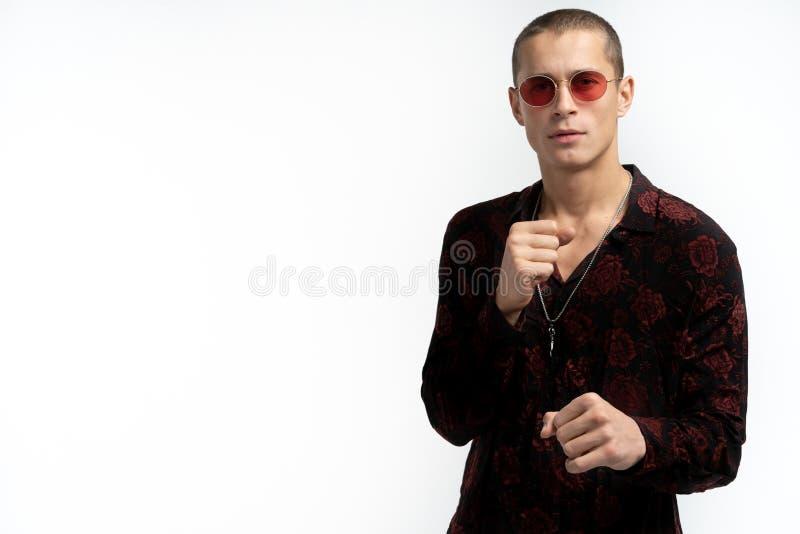 De aantrekkelijke jonge mens in in modieus zwart overhemd met roze druk in rode zonnebril houdt vuisten vooraan als hem royalty-vrije stock foto's