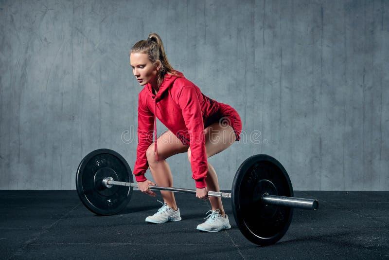 De aantrekkelijke jonge sportieve vrouw werkt in gymnastiek uit De spiervrouw hurkt met barbell royalty-vrije stock foto
