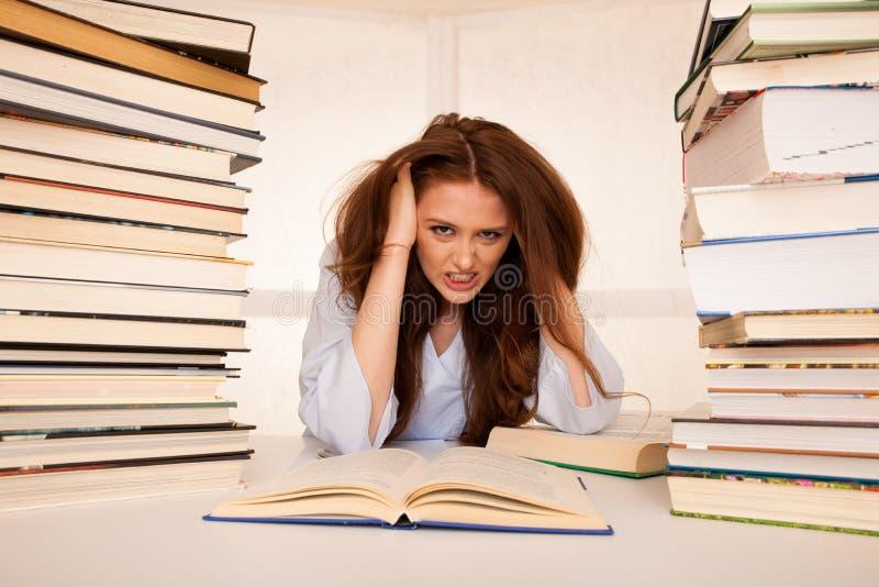 De aantrekkelijke jonge studente undre beklemtoont terwijl het studiing voor e stock foto
