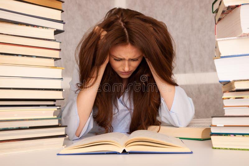 De aantrekkelijke jonge studente undre beklemtoont terwijl het studiing voor e stock fotografie