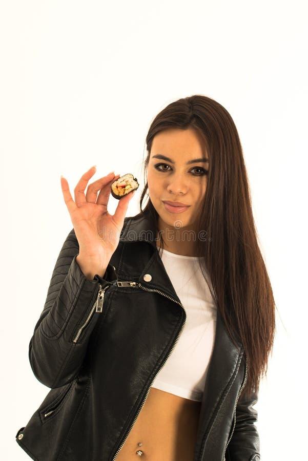 De aantrekkelijke jonge sushi van de vrouwenholding in haar hand royalty-vrije stock fotografie
