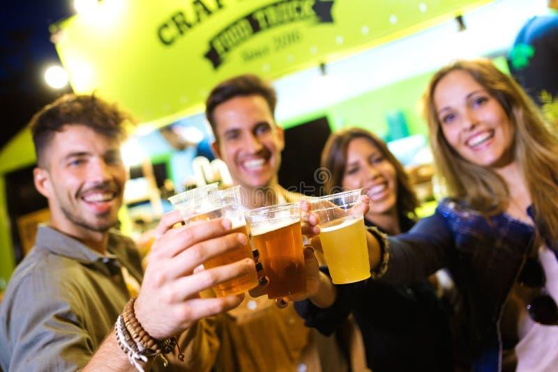 De aantrekkelijke jonge vrienden die camera bekijken terwijl het roosteren met bier eten binnen markt in de straat royalty-vrije stock afbeeldingen