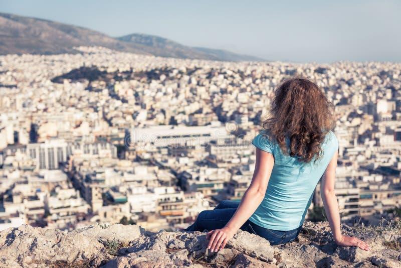 De aantrekkelijke jonge vrouw bekijkt cityscape Athene, Griekenland stock afbeeldingen