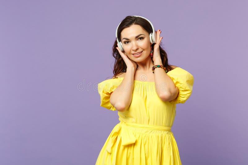 De aantrekkelijke jonge vrouw die in die gele kleding camera, luistert muziek, zettend handen op hoofdtelefoons kijken op pastelk stock afbeeldingen