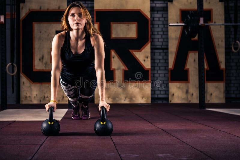 De aantrekkelijke jonge vrouw die van de gymnastiekgeschiktheid opdrukoefeningen doen stock foto