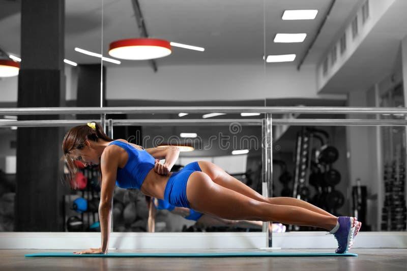De aantrekkelijke jonge vrouw doet plankoefening terwijl het uitwerken in gymnastiek royalty-vrije stock afbeelding