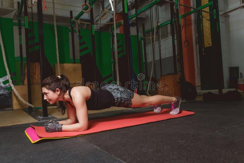 De aantrekkelijke jonge vrouw doet plankoefening terwijl het uitwerken in gymnastiek royalty-vrije stock foto