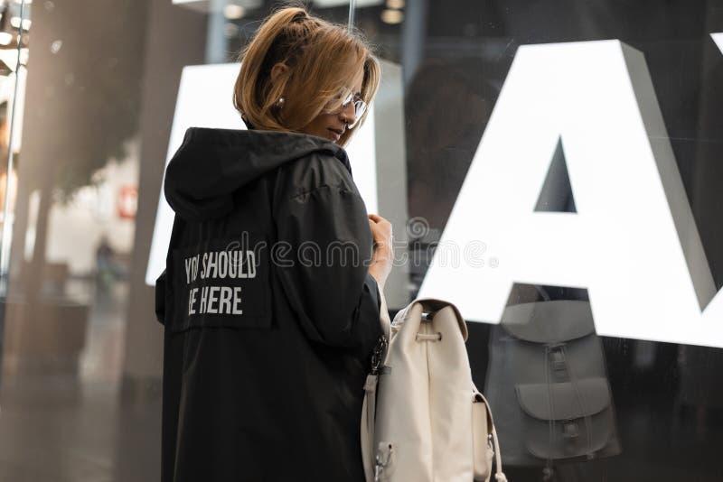 De aantrekkelijke jonge vrouw in een modieuze regenjas in uitstekende glazen met een modieuze witte leerrugzak bevindt zich stock afbeelding