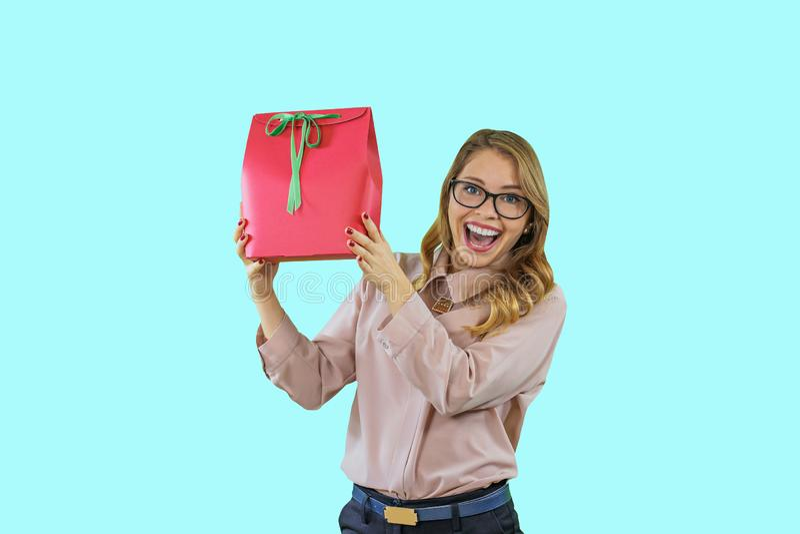De aantrekkelijke jonge vrouw in glazen houdt een gift in een rode doos met een groen lint houdend de gift omhoog glimlachend bij royalty-vrije stock afbeelding