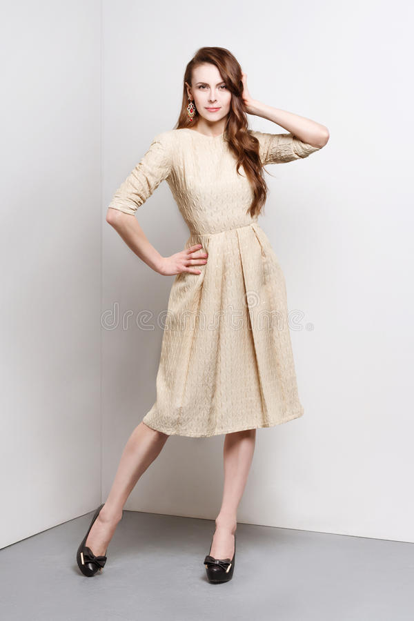 De aantrekkelijke jonge vrouw in gouden kleding bevindt zich op manier stelt stock foto's