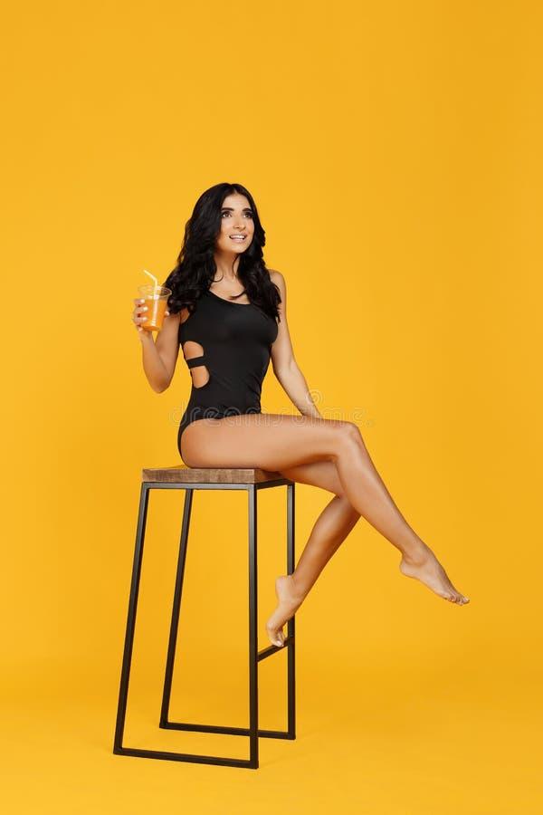 De aantrekkelijke jonge vrouw kleedde zich in het zwarte zwempak stellen op de barstoel en het houden van jus d'orange over oranj stock fotografie