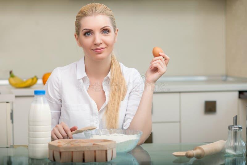 De aantrekkelijke jonge vrouw kookt in keuken stock afbeelding