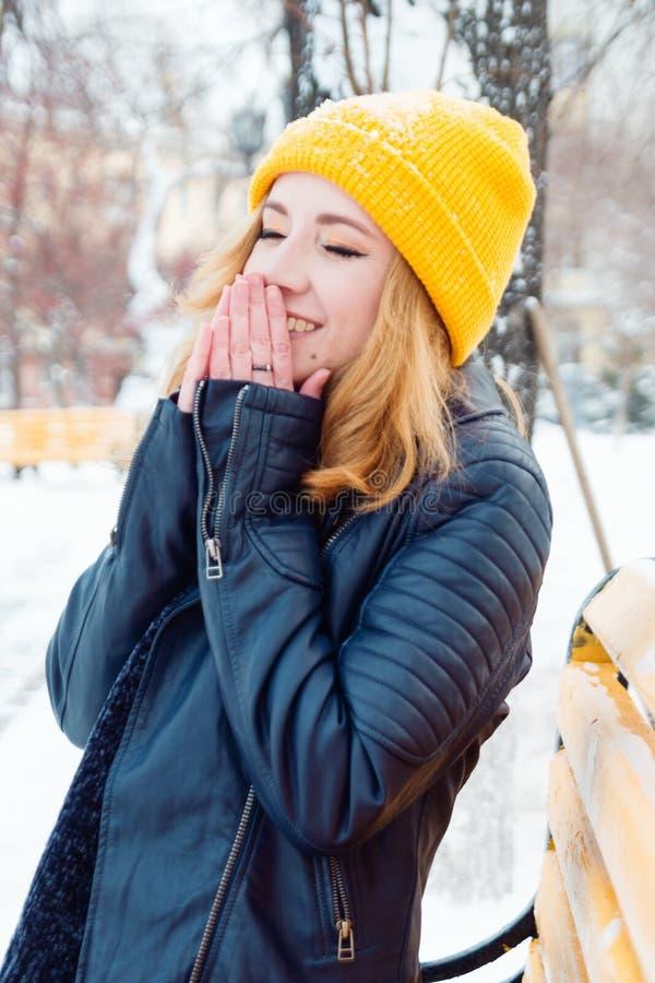 De aantrekkelijke jonge vrouw met blond haar in een gele breiende hoed verwarmt haar indient het de winterpark royalty-vrije stock fotografie