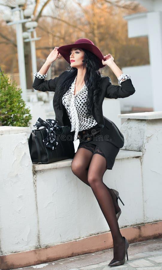 De aantrekkelijke jonge vrouw met Bourgondië kleurde grote hoed in herfstmanierschot Mooie dame in zwarte uitrusting met korte ro stock fotografie