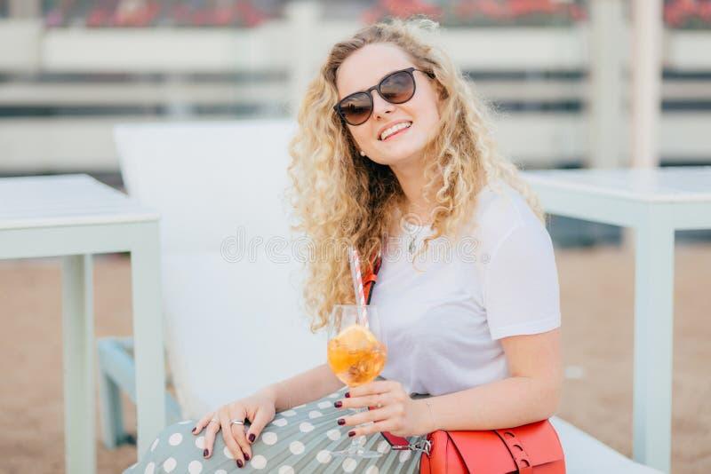 De aantrekkelijke jonge vrouw met golvend haar, draagt zonnebril, heeft goede rust tijdens de zomertijd, houdt verse drank, heeft royalty-vrije stock foto