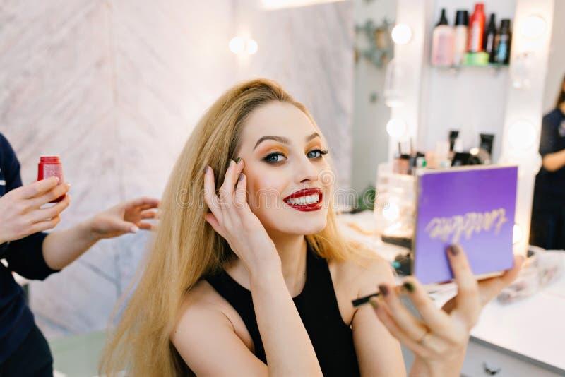 De aantrekkelijke jonge vrouw met lang blondehaar, rode lippen die aan camera met spiegel glimlachen dient binnen schoonheidssalo royalty-vrije stock fotografie