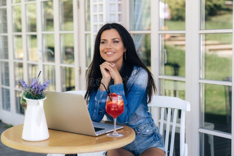 De aantrekkelijke jonge vrouw zit bij een lijst in een koffie, kijkt rond, en lacht Het model heeft een Europese donkere verschij stock foto