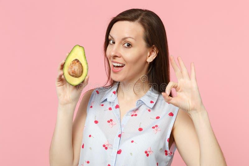 De aantrekkelijke jonge vrouw in de zomerkleren die O.K. gebaar tonen, houdt vers rijp groen die avocadofruit op roze pastelkleur royalty-vrije stock fotografie