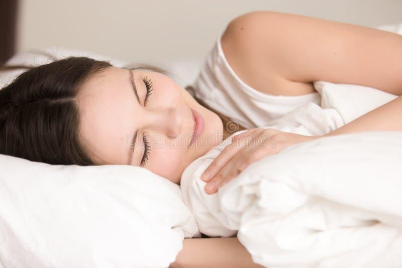 De aantrekkelijke jonge vrouwenslaap comfortabel in bed, sluit omhoog hea royalty-vrije stock afbeelding